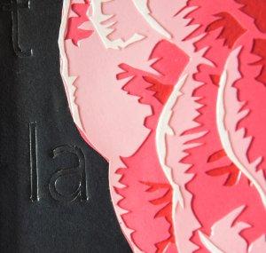 Gros plan sur le travail de découpe des pétales et sur les mots gravés dans le papier noir. Découpage collage par Carole b.
